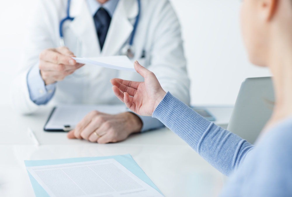 Doctor in his office giving a medical prescription to the patient, healthcare concept